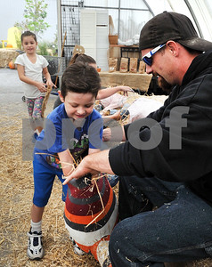 Mikie Pozzie (5) and his sister Kylie (7) help their dad Mike Pozzie of Melrose Park make a scarecrow at Wannamaker's Home and Garden Fall Festival on Saturday, Septemer 24 in Downers Grove.  Steve Bittinger for Shaw Media