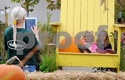 Nursery associate Christine Thompson takes a photo of Violet  Asseltine (left), 3, and her sister Ally, 5, at Wannamaker's Home and Garden Fall Festival on Saturday, Septemer 24 in Downers Grove.  Steve Bittinger for Shaw Media