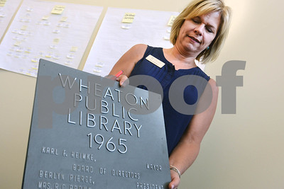 Wheaton Public Library Director Betsy Adamowski holds up a plaque in her office Thursday, Sept. 1, from the time that the current library was built. The library is celebrating its 125th anniversary this year. There will be a presentation about the library's past, present and future at 7 p.m. Sept. 26. Mark Busch - mbusch@shawmedia.com
