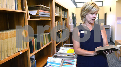 Wheaton Public Library Director Betsy Adamowski looks at some of the books from the original library's collection Thursday, Sept. 1. The library is celebrating its 125th anniversary this year. There will be a presentation about the library's past, present and future at 7 p.m. Sept. 26. Mark Busch - mbusch@shawmedia.com