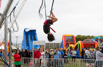 Mike Greene - For Shaw Media  Emily Lawson, 11 of Bensenville, hangs upside-down while enjoying a bungee trampoline during the 2nd annual Harvard Balloon Festival Saturday, September 2, 2017 at Milky Way Park in Harvard. This year's event features hot air balloon rides, food vendors, helicopter rides, inflatables, live entertainment, games and more.