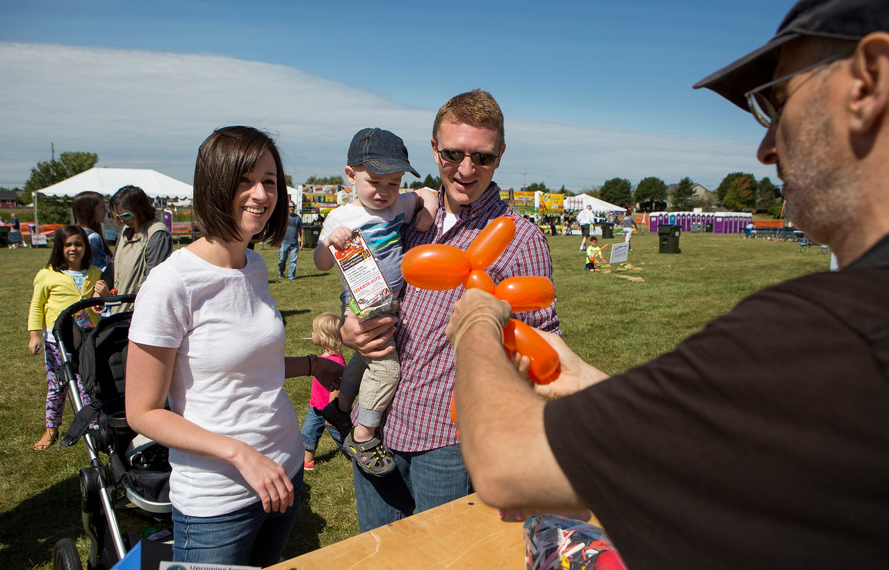 Mike Greene - For Shaw Media  Kelly, left, Johnnie, 2, and John Bradley, of Crystal Lake, wait to receive a balloon animal from Gary Kantor during the 16th annual Summer Sunset Festival Saturday, September 2, 2017 at Sunset Park in Lake in the Hills. This year's event featured a parade, carnival rides, a craft show, Battle of the Bands, a classic and custom car show, horsehoe and bags tournaments, the Sunset 5K and fireworks.