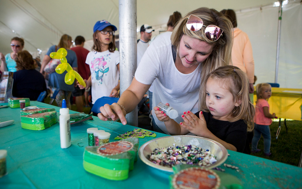 """Mike Greene - For Shaw Media  Allison Maroney, of Lake in the Hills, helps her daughter Nora, 2, craft a """"Christmas in September"""" ornament during the 16th annual Summer Sunset Festival Saturday, September 2, 2017 at Sunset Park in Lake in the Hills. This year's event featured a parade, carnival rides, a craft show, Battle of the Bands, a classic and custom car show, horsehoe and bags tournaments, the Sunset 5K and fireworks."""