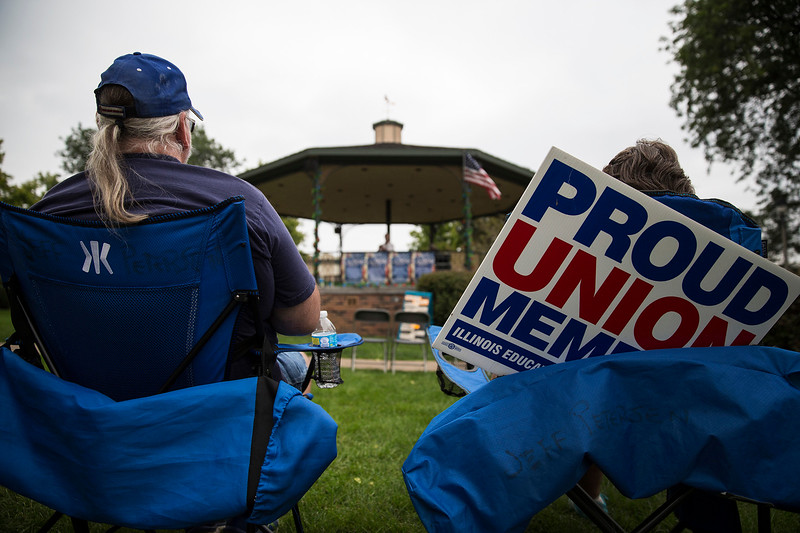 Rod Peterson and Stacey Pyne, from Island Lake, listen to speakers during a Labor Day Celebration in Woodstock Square on Monday, September 4, 2017 in Woodstock, Illinois. The event is held by the McHenry County Progressives in Support of Working Families. John Konstantaras photo for Shaw Media