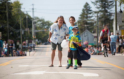Mike Greene - For Shaw Media  Marilyn Shepit, left, Andrew Shepit, center, 8, and Parker Hinga, 6 of McCullom Lake, see if they can catch a glimpse of the oncoming parade before the start of the 45th annual Saufen und Spiel Parade Sunday, September 10, 2017 in Johnsburg. This year's event featured a variety of food vendors, inflatables, live music, as well as the annual Cow Drop raffle.