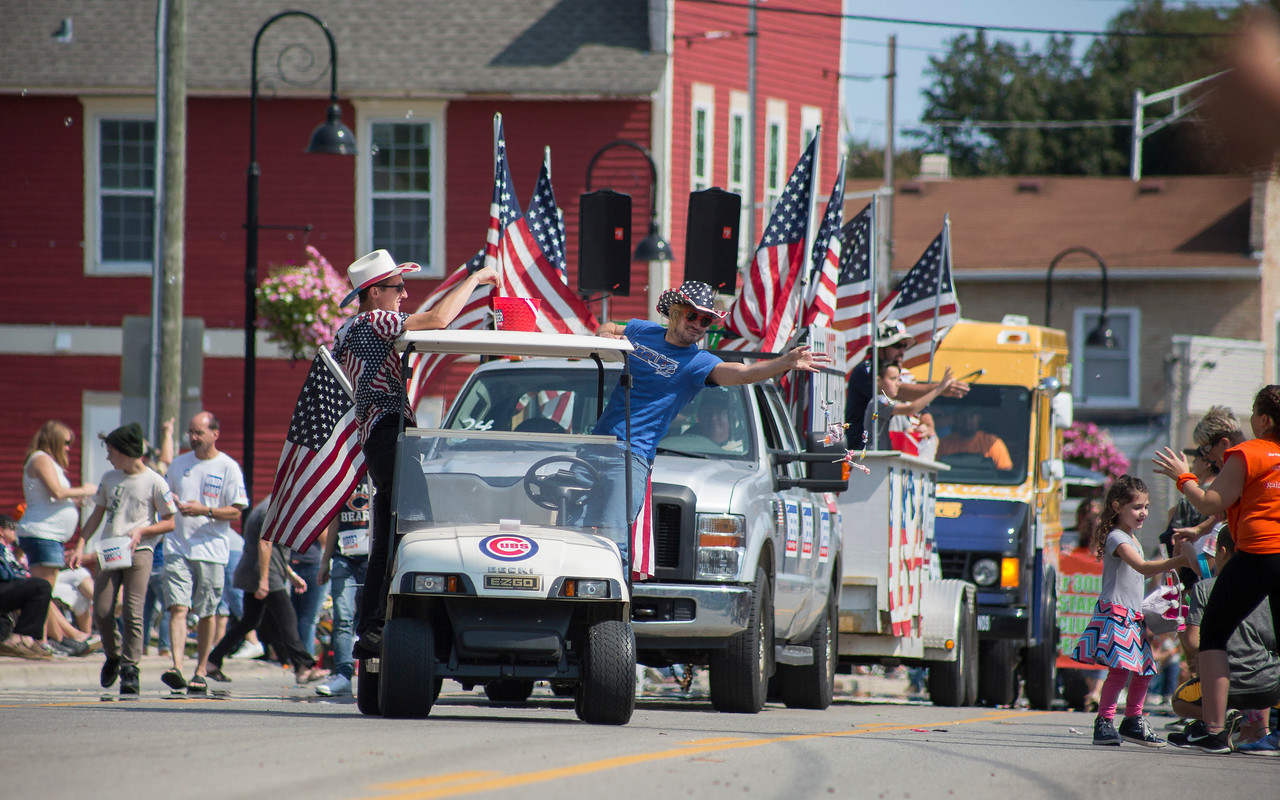 Mike Greene - For Shaw Media  Parade participants toss candy to the crowd during the 45th annual Saufen und Spiel Parade Sunday, September 10, 2017 in Johnsburg. This year's event featured a variety of food vendors, inflatables, live music, as well as the annual Cow Drop raffle.