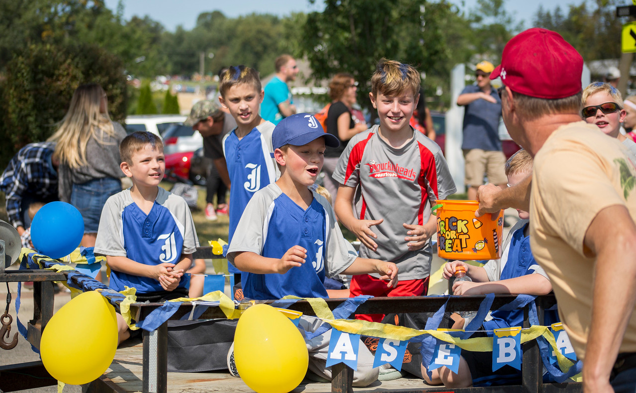 Mike Greene - For Shaw Media  Members of the Johnsburg Little League float get a re-supply on their candy during the 45th annual Saufen und Spiel Parade Sunday, September 10, 2017 in Johnsburg. This year's event featured a variety of food vendors, inflatables, live music, as well as the annual Cow Drop raffle.