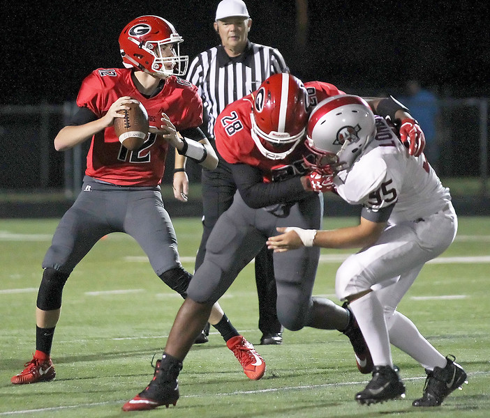 Candace H. Johnson-For Shaw Media Grant's Matt McGraw looks to pass as Kenyon Jones defends against Antioch's Robert Londono in the fourth quarter at Grant Community High School in Fox Lake.
