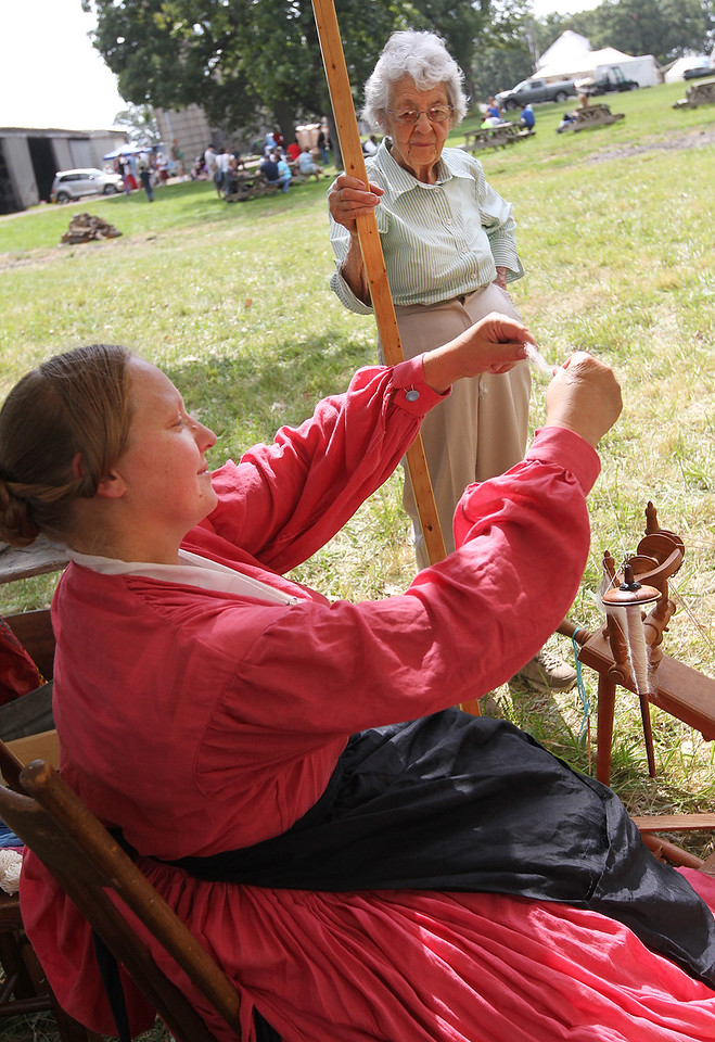 Candace H. Johnson-For Shaw Media Laurel Denny, of Grayslake listens to Sarah Zeien, of Trevor, Wis., talk about a drop spindle as she portrays civilian life during Hainesville's Civil War Encampment & Battle at the Northbrook Sports Club in Hainesville.