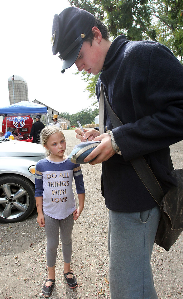 Candace H. Johnson-For Shaw Media Brianna Boles, 5, of Kenosha, Wis., gets an autograph from Jordan Brendemuehl, 16, of Milwaukee, Wis., as a Union soldier with the 45th Illinois Infantry during Hainesville's Civil War Encampment & Battle at the Northbrook Sports Club in Hainesville.