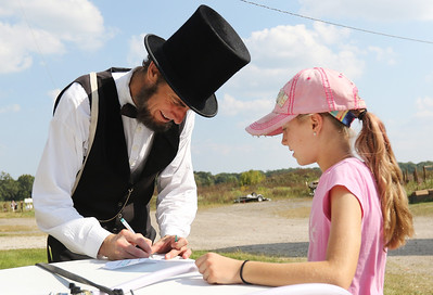 Candace H. Johnson-For Shaw Media Kevin Wood, of Oak Park, as President Abraham Lincoln signs his autograph for Sophia Strine, 10, of Round Lake during Hainesville's Civil War Encampment & Battle at the Northbrook Sports Club in Hainesville.