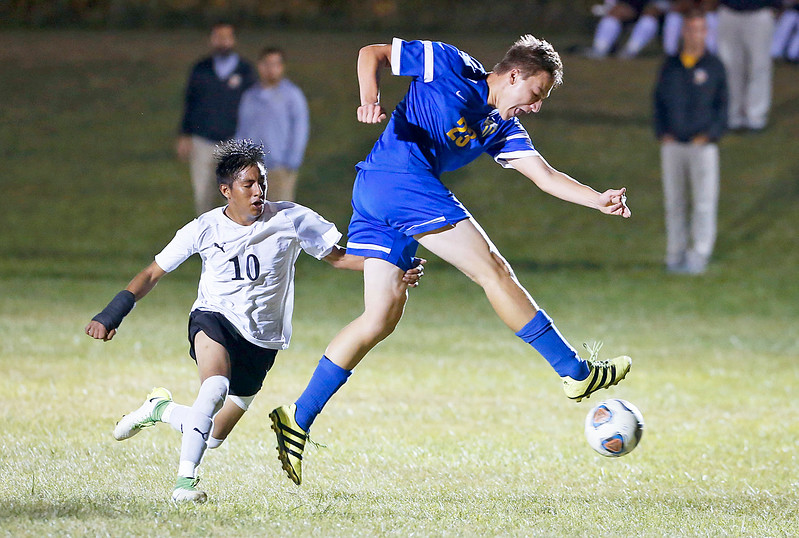 John Konstantaras - for Shaw Media Adrian Gorostieta (10) from Harvard grabs onto Mason Sobiesk (23) from Johnsburg as he clears a ball in front of his goal during the second half of their game on Tuesday, September 19, 2017 in Harvard, Illinois. The Hornets defeated the Skyhawks 1-0.