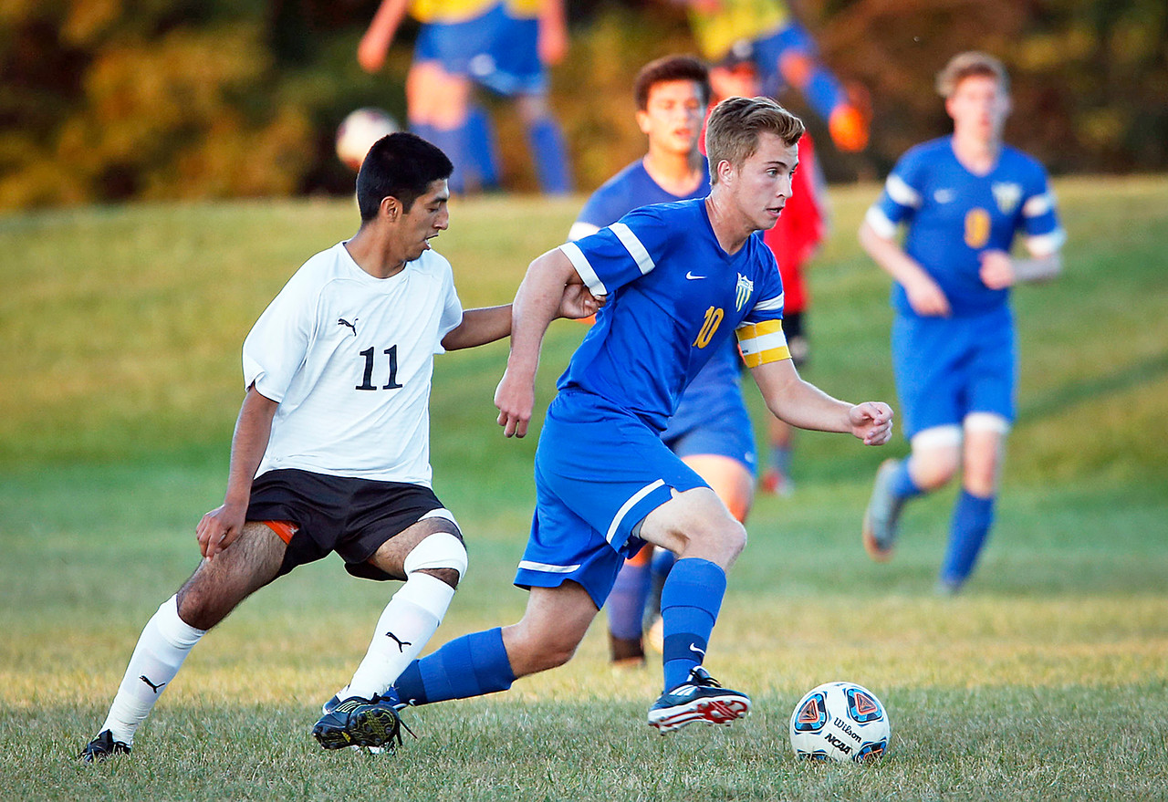 Dean Wiersum (10) from Johnsburg runs the ball past Gabriel Popoca (11) from Harvard during the first half of their game on Tuesday, September 19, 2017 in Harvard, Illinois. The Hornets defeated the Skyhawks 1-0.
