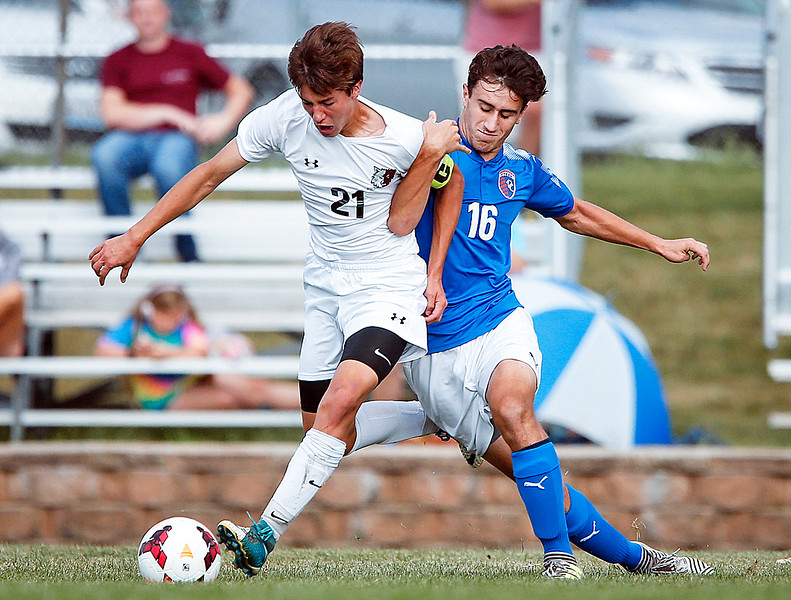 Erik Truitt (21) from Prairie Ridge and Julian Ajroja (16) from Dundee-Crown battle for a ball during the first half of their game at Prairie Ridge High School on Tuesday, September 26, 2017, in Crystal Lake, Illinois. The Chargers defeated the Wolves 1-0 in overtime. John Konstantaras photo for Shaw Media