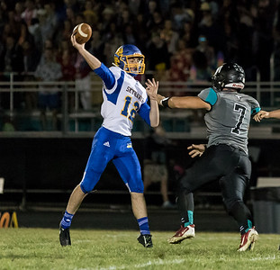 Johnsburg High School quarterback Adam Jayko throws a pass down field over Woodstock North's Derek Freeman Friday, September 29, 2017 at Woodstock North High School. Johnsburg goes on to win the conference matchup 41-7. KKoontz – For Shaw Media
