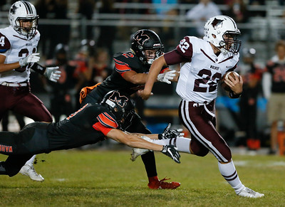 Samson Evans (22) from Prairie Ridge runs for a first down as Nicco Lorenzo (3) and Kennedy Kosmalski (2) from McHenry chase him during the first quarter of their game at McHenry High School on Friday, September 29, 2017 in McHenry, Illinois. John Konstantaras photo for Shaw Media