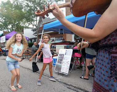 Candace H. Johnson-For Shaw Media Sammy Hernandez, 11, of Round Lake and her cousin Olivia Jones, 9, of Wauconda dance to Celtic music played by Wendy Maland, of Wauconda, a roaming violinist, during Wauconda's 19th Annual Street Dance on Main Street in Wauconda.