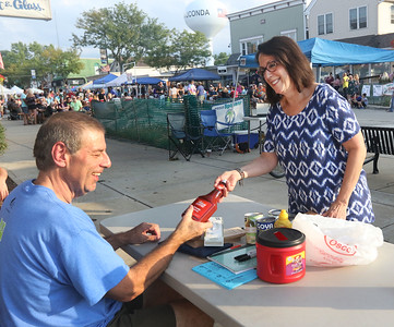 Candace H. Johnson-For Shaw Media Kevin Barnes, of Wauconda, with the Wauconda Food Pantry, receives some canned goods and tomato ketchup from Pam Verdico, of Island Lake during Wauconda's 19th Annual Street Dance and Food Drive on Main Street in Wauconda.