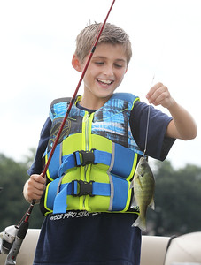 Candace H. Johnson-For Shaw Media Tyler Giacomino, 9, of Wauconda is all smiles on a boat as he catches a bluegill fish during the 13th Annual Kids Fishing Derby in Bangs Lake in Wauconda. The event was hosted by Wauconda Boat and sponsored by the Bangs Lake Advisory Committee. (9/2/18)