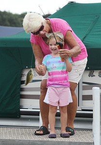 Candace H. Johnson-For Shaw Media Jean Schindler, of Wauconda helps her granddaughter, Riley Swanson, 3, of Lisle bring in a bluegill fish she just caught fishing on a pier during the 13th Annual Kids Fishing Derby in Bangs Lake in Wauconda. The event was hosted by Wauconda Boat and sponsored by the Bangs Lake Advisory Committee. (9/2/18)