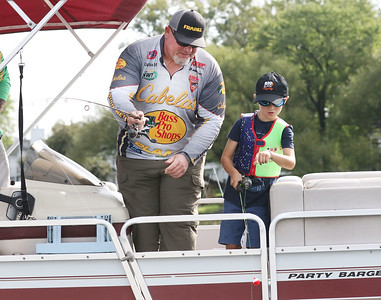 Candace H. Johnson-For Shaw Media Bob Bachler, of Wauconda, a representative with Bass Pro Shops, Cabela's and Plano, helps Jake Miczek, 6, of Wauconda fish off of a boat during the 13th Annual Kids Fishing Derby in Bangs Lake in Wauconda. The event was hosted by Wauconda Boat and sponsored by the Bangs Lake Advisory Committee. (9/2/18)