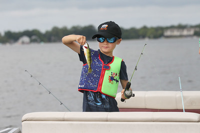 Candace H. Johnson-For Shaw Media Jake Miczek, 6, of Winnetka looks at a perch he just caught fishing off of a boat in Bangs Lake during the 13th Annual Kids Fishing Derby in Wauconda.  The event was hosted by Wauconda Boat and sponsored by the Bangs Lake Advisory Committee. (9/2/18)
