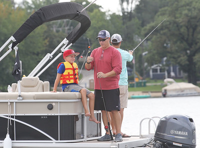 Candace H. Johnson-For Shaw Media Parker Bufton, 9, of Volo watches his father, Steve, bait a hook on his fishing pole as they fish from a boat during the 13th Annual Kids Fishing Derby in Bangs Lake in Wauconda. Steve Diver, of Wauconda stood beside them. The event was hosted by Wauconda Boat and sponsored by the Bangs Lake Advisory Committee. (9/2/18)