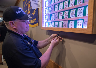 McHenry Veterans of Foreign Wars Post 4600 Cmdr. Dwane Lungren unlocks the case selecting envelope number 38 to be opened at the Queen of Hearts raffle Tuesday, September 11, 2018 in McHenry. The card in the envelope was the ten of spades forcing a draw-down to the raffle next Tuesday night. KKoontz – For Shaw Media