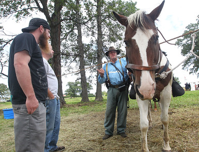 Candace H. Johnson-For Shaw Media Ben Tuggle and his father, Frank, both of Lakemoor talk with Kevin Wright, of Peotone as he stands next to his horse named, Jack, during Hainesville's Civil War Encampment & Battle at the Northbrook Sports Club on Hainesville Road.Wright portrayed a Confederate soldier with the 3rd Tennessee Calvary. (9/9/18)