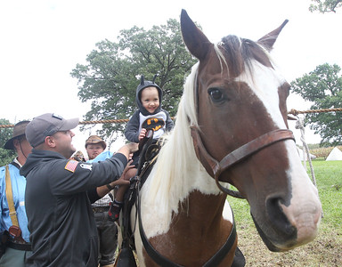 Candace H. Johnson-For Shaw Media Eric Weaver, of Round Lake holds on to his son, Marshal, 3, as he sits on a 3rd Tennessee Calvary horse named, Jack, during Hainesville's Civil War Encampment & Battle at the Northbrook Sports Club on Hainesville Road. (9/9/18)