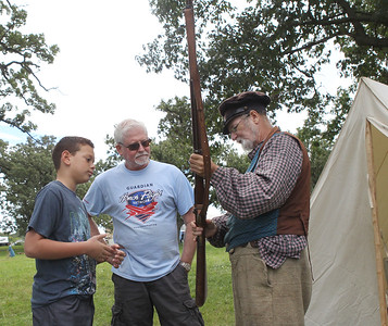 Candace H. Johnson-For Shaw Media Micah Zahir, 10, and his grandfather, Jim Jesse, both of Hainesville talk with Mike Miller, of Woodridge, about his 1853 Enfield rifle musket during Hainesville's Civil War Encampment & Battle at the Northbrook Sports Club on Hainesville Road. Miller portrayed a Confederate soldier named, Mordai Dettweiller, from the 154th Tennessee Infantry Company K.(9/9/18)