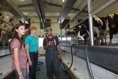 Candace H. Johnson-For Shaw Media Jessi VonHelms, 12, of McHenry and her mother, Dixie, talk to Elijah Pacheco, of Turlock Calif., an intern, in the milk barn at the Golden Oaks Farm in Wauconda during the Lake County Farm Stroll.(9/16/18)