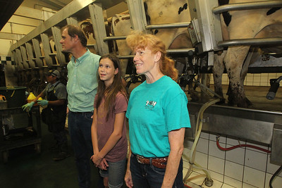 Candace H. Johnson-For Shaw Media John and Dixie VonHelms, of McHenry and their daughter, Jessi, 12, (center) watch dairy cows produce milk using milk machines in the milk barn at the Golden Oaks Farm during the Lake County Farm Stroll in Wauconda. (9/16/18)