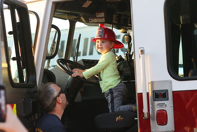 Candace H. Johnson-For Shaw Media Daniel Billings, of Grayslake watches his son, Fenton, 2, sit in a Gurnee Fire Dept. fire truck during Touch-A-Truck at the Hunt Club Park Community Center in Gurnee. (9/14/18)