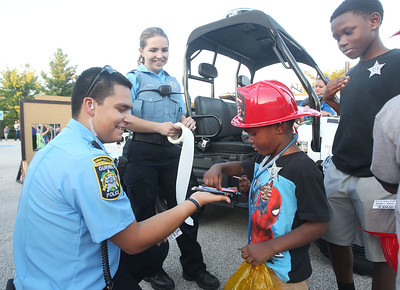 Candace H. Johnson-For Shaw Media Armando Martinez and Stephanie Auth, both Village of Gurnee Community Service Officers, give pencils and stickers to Peyton Walthour, 4, of Gurnee and his brother, Sedrick McMillan, 10, during Touch-A-Truck at the Hunt Club Park Community Center in Gurnee. (9/14/18)