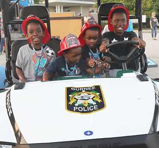 Candace H. Johnson-For Shaw Media Tmarrion Walthour, 5, of Gurnee sits in a Gurnee Police Department's ATV with his brothers, Daijon, 2, Peyton, 4, and Sedrick McMillan, 10, during Touch-A-Truck at the Hunt Club Park Community Center in Gurnee. (9/14/18)