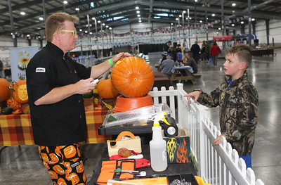 "Candace H. Johnson-For Shaw Media Robert Childers, of Lombard, master pumpkin carver, works on a pumpkin titled, ""Monkey Man,"" as he talks with Teige McMillon, 6, of Wildwood during the Farm Heritage & Harvest Festival at the Lake County Fairgrounds in Grayslake. (9/22/18)"
