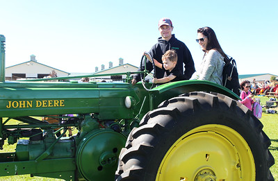 Candace H. Johnson-For Shaw Media Sebastian Loeffler, 4, sits next to his mother, Renate, as he drives a 1946 John Deere A tractor with the help of Scott Kaminski, 25, all of Grayslake during the Farm Heritage & Harvest Festival at the Lake County Fairgrounds in Grayslake. (9/22/18)