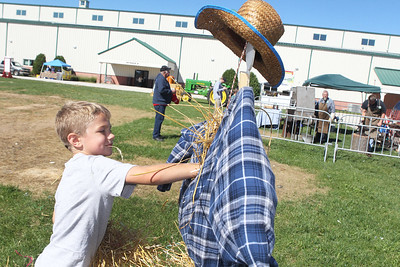 Candace H. Johnson-For Shaw Media Shane McMillon, 7, of Trevor, Wis., stuffs a scarecrow with hay during the Farm Heritage & Harvest Festival at the Lake County Fairgrounds in Grayslake. (9/22/18)