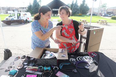 Candace H. Johnson-For Shaw Media Christin Haka with Paparazzi accessories helps Jennifer Murray, both of Antioch, pick out some jewelry to go with a dress she is wearing to a wedding at the Antioch Farmer's Market in front of the Bandshell on Skidmore Drive in downtown Antioch. The farmer's market runs every Thursday from 2-6pm. until September 26th. (8/29/19)