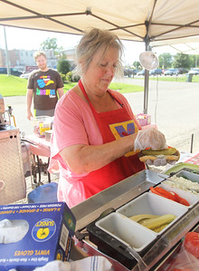 Candace H. Johnson-For Shaw Media Candy Gandolfi-Martin, of Mundelein makes a veggie-style Chicago hot dog with mustard, relish, onions, tomatoes, pickles, peppers and a splash of celery salt for a customer in her Famous Frankie's Hot Dogs stand at the Antioch Farmer's Market in front of the Bandshell on Skidmore Drive in downtown Antioch. The farmer's market runs every Thursday from 2-6pm. until September 26th. (8/29/19)