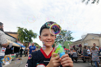 Candace H. Johnson-For Shaw Media Ryan Landmeier, 8, of Island Lake blows bubbles with a bubble machine he was helping to sell to raise money for a non-profit called, K9s4U Dog Rescue, during the Wauconda Street Dance on Main Street in Wauconda. (8/31/19)