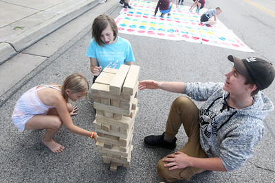 Candace H. Johnson-For Shaw Media Madelynn Lindquist, 7, of Lakemoor plays Jenga with Isabelle Billen, 14, and Dennis Kloss, 15, both of Wauconda during the Wauconda Street Dance on Main Street in Wauconda. (8/31/19)