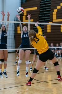 #13 Meredith Giusgtino spikes the ball through the Trojanes defense in the semi final game.