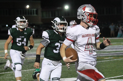 Candace H. Johnson-For Shaw Media Mundelein's quarterback Isaac Wellman (#4) carries the ball past Grayslake Central's Payton Waigand in the second quarter at Grayslake Central High School. Mundelein won 31-13. (9/6/19)