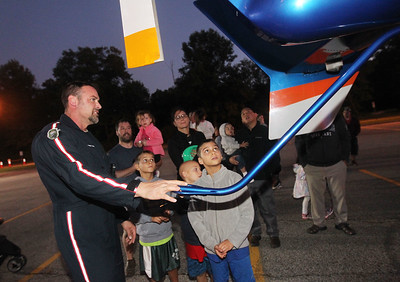 Candace H. Johnson-For Shaw Media Pilot Tyler Butterfield holds on to the tail roter of the Flight for Life helicopter he just landed as he talks with children about the aircraft during the Gurnee Park District's 10th Annual Touch-A-Truck at the Hunt Club Park Community Center in Gurnee. (9/13/19)