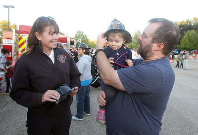 Candace H. Johnson-For Shaw Media Tammie Hilliard, fire inspector with the Gurnee Fire Department, gives a junior firefighter hat to Isabel Whitlatch, 2, of Grayslake as she gets some help putting it on from her father, Ryan, during the Gurnee Park District's 10th Annual Touch-A-Truck at the Hunt Club Park Community Center in Gurnee. (9/13/19)