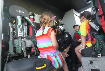 Candace H. Johnson-For Shaw Media Evan Locklear, firefighter paramedic with the Gurnee Fire Department, talks to children about the SCBA mask he was wearing, a breathing apparatus used to battle a fire, as they sit in the Station 2 fire engine during the Gurnee Park District's 10th Annual Touch-A-Truck at the Hunt Club Park Community Center in Gurnee. (9/13/19)