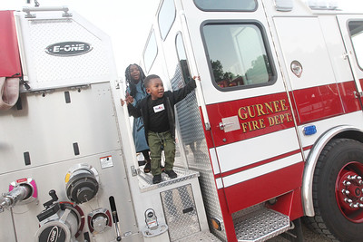Candace H. Johnson-For Shaw Media Amarii Jones, 9, of Gurnee and her brother, Naeem, 3, climb on a Gurnee Fire Department fire truck during the Gurnee Park District's 10th Annual Touch-A-Truck at the Hunt Club Park Community Center in Gurnee. (9/13/19)