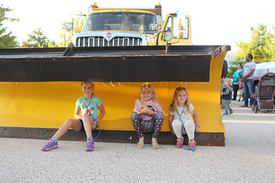 Candace H. Johnson-For Shaw Media Colleen Dilger, 8, of Hainesville and her sisters, Anna, 6, and Heidi, 4, sit in the shovel of an Illinois Tollway truck during the Gurnee Park District's 10th Annual Touch-A-Truck at the Hunt Club Park Community Center in Gurnee. (9/13/19)